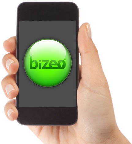 Hand holding an iPhone showing green Bizeo monitor